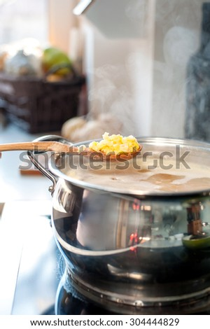 Saucepan and wooden spoon with split pea. Boiling broth with steam. Making soup. - stock photo