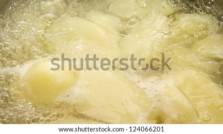 Saucepan full of boiling potatoes - stock photo