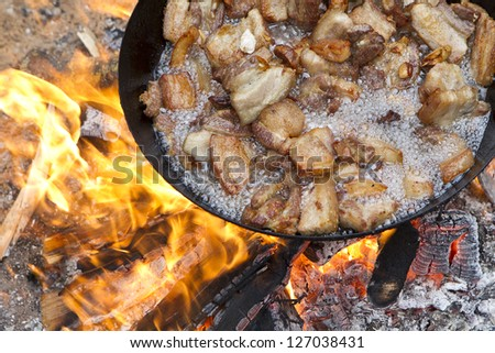 saucepan of bacon frying in fire - stock photo