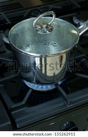 Saucepan on a gas cooker hob - stock photo