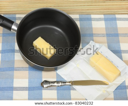 Saucepan with melting cooking butter in it, and a butter stick wrapped in foiled paper, on table - stock photo