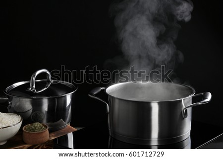 Saucepan with steam on black background