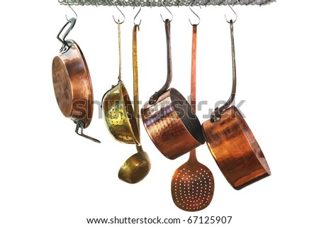saucepans hanging from a rack in a traditional style kitchen - stock photo