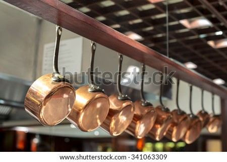 saucepans hanging from a rack in the  kitchen - stock photo