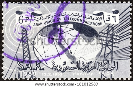 SAUDI ARABIA - CIRCA 1961: A stamp printed in Saudi Arabia issued for the 6th Anniversary of Arab Telecommunications Union shows telecommunication pylons and map, circa 1961.  - stock photo