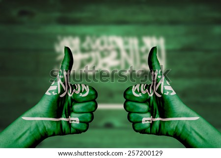 Saudi Arabia flag painted on female hands thumbs up with blurry wooden background - stock photo