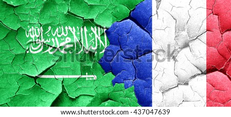 Saudi Arabia flag with France flag on a grunge cracked wall