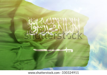 Saudi Arabia waving flag against blue sky with sunrays - stock photo