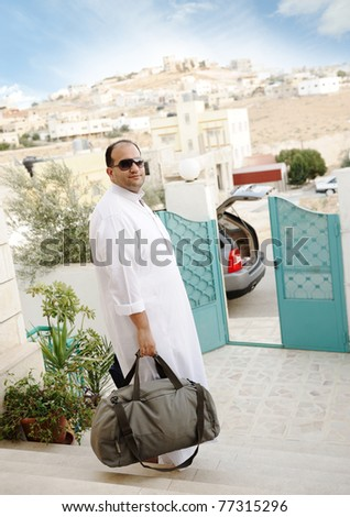 Saudi arabic businessman traveling with his car, holding a bag on stairs - stock photo