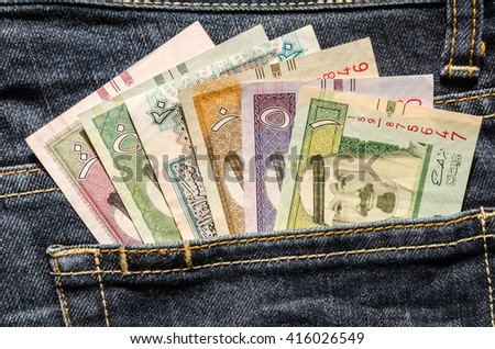 Saudi Riyals banknotes in the back pocket of blue jeans - stock photo
