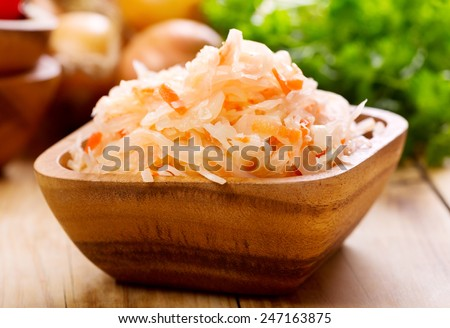 sauerkraut in a bowl on wooden table - stock photo