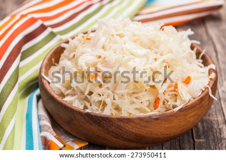 sauerkraut in a wooden bowl on the table - stock photo