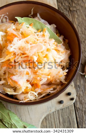 Sauerkraut in ceramic bowl on rustic wooden table with spices, traditional rustic winter food - stock photo