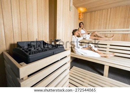 Sauna heater in a cozy sauna and girls relaxing in the background - stock photo