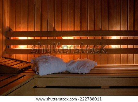 Sauna interior with white bathrobes leaving room for type.  - stock photo