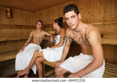 Sauna spa therapy young people group in warm wooden room white towel - stock photo