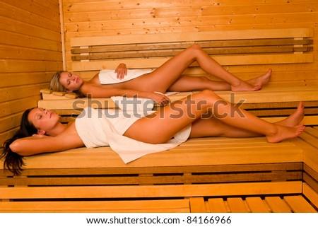 Sauna two healthy beautiful women relaxing lying wrapped in towel - stock photo