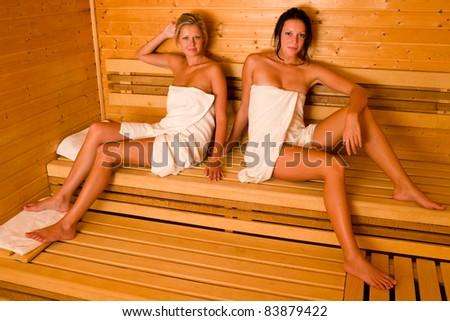 Sauna two healthy beautiful women relaxing sitting wrapped in towel - stock photo