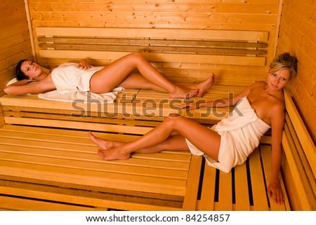 Sauna with two healthy, beautiful women relaxing - stock photo