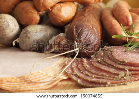 Sausage and meat assortment on cutting board closeup - stock photo