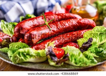 Sausage. Chorizo sausage. Raw smoked sausage with vegetable decoration.Lettuce salad herb rosemary tomato garlic olive oil. - stock photo