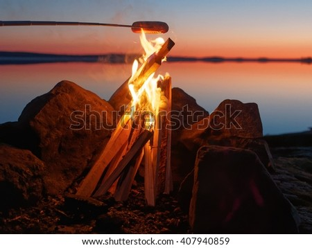 Sausage grilled on the campfire at sunset. Still water of the lake on the background with atmospheric evening light. - stock photo