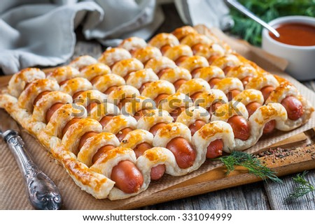 Sausage in the dough with ketchup on the wooden background - stock photo