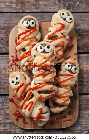 Sausage meatball mummies wrapped in dough and baked. Scary halloween celebration party food covered with fake blood sauce decoration. Vintage wooden background. Rustic style - stock photo