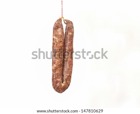 Sausage on a string symbolising a Dutch proverb to lure someone with a sausage - stock photo