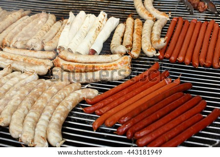 Sausage party. Barbecue large grill outdoors. Cookout bbq food. Big roasted pork bratwurst german sausages, white polish kielbasa. Meat grilled meal. Street food, fast food. Tasty snack, sausages. - stock photo