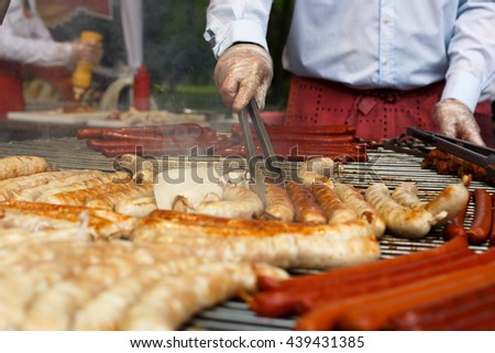 Sausage party. Chef cooking at barbecue big grill outdoors. Cookout bbq food. Roasted pork bratwurst german sausages, white polish kielbasa. Meat grilled meal. Street food, fast food. Tasty sausages. - stock photo