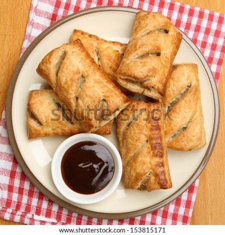 Sausage rolls with brown sauce dip. - stock photo