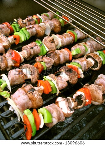 Sausage shish kebabs on skewers, cooking on the grill. - stock photo