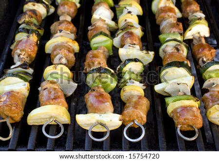Sausage shish kebabs on skewers, cooking on the grill.