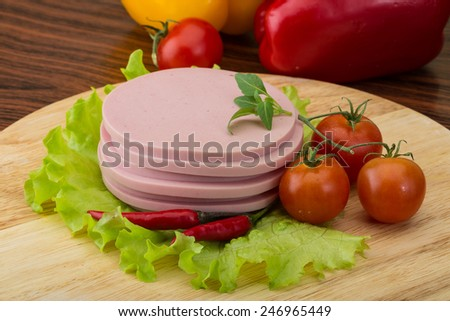 Sausage with salad leaves, tomato, pepper and basil - stock photo