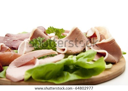 Sausage with salad onto plates - stock photo