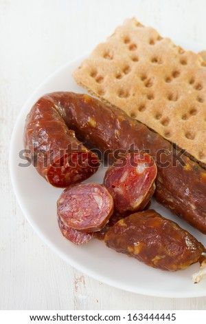 sausage with toasts on white plate