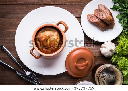 Sausage Yorkshire pudding in the baking pot on wooden background top view. English Toad in the Hole, a traditional British dish. - stock photo