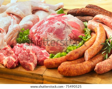 Sausages and meat on a cutting board - stock photo