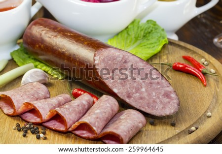 sausages on a wooden plate with vegetables in a restaurant - stock photo