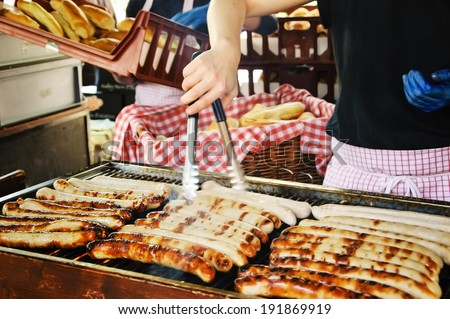 Sausages on the grill, hands of the seller and a pile of  buns at background. Hot dogs stall at  famous Borough Food Market (London, England). Selective focus on the sausages at the left corner. - stock photo