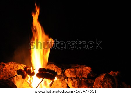 Sausages on the stick in fire. Night campfire - stock photo