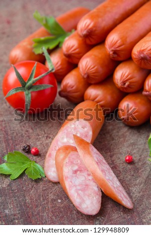 Sausages on wooden board with cherry tomato - stock photo