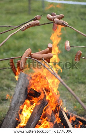 sausages roasting over fire flames - stock photo