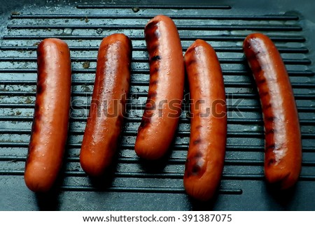 Sausages with brown grill marks in a grill pan  - stock photo
