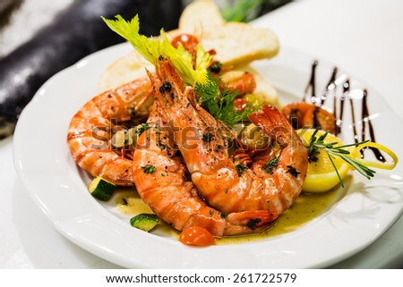 Saute shrimps with vegetables and lemon on white plate in the restaurant. - stock photo