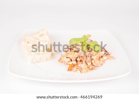 Sauteed chanterelle with cream and garlic and some white bread on a plate decorated with basil