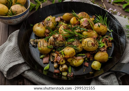 Sauteed new potatoes with bacon and herbs - stock photo