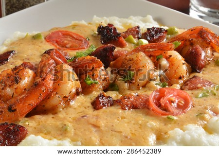 Sauteed shrimp in a creole butter sauce with peppers and vegetable medley on grits - stock photo