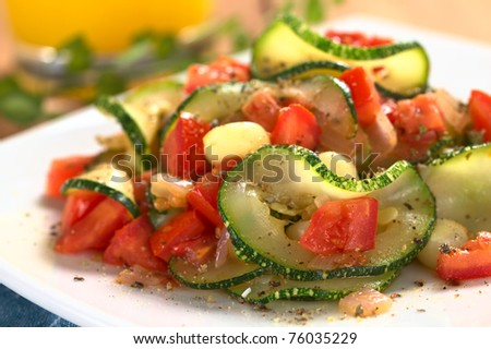 Sauteed zucchini slices, tomato cubes, onion and cooked corn grains with dried herbs and black pepper (Selective Focus, Focus on the front of the zucchini slice and tomato piece in the front) - stock photo